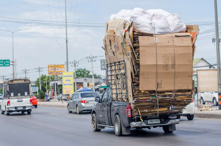 Samut Sakhon, Thailand - July 2019: Small trucks carrying recycled paper boxes on Phutthasakorn Road on July 28, 2019 in Samut Sakhon, Thailand. Sajtókép