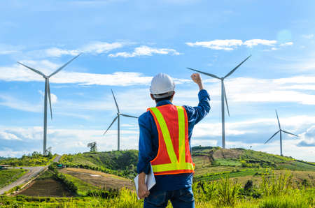Successful engineer standing with wind turbine on blue sky background.