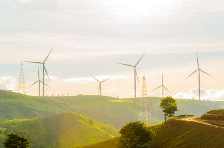 Wind turbines produce electricity with sunlight during sunset background.