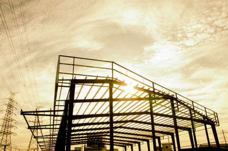 Metal frame of building construction on sunrise background, Steel structure is under construction. Stock fotó