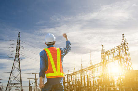 Successful engineer standing at the power substation against the sunrise background. Stock fotó