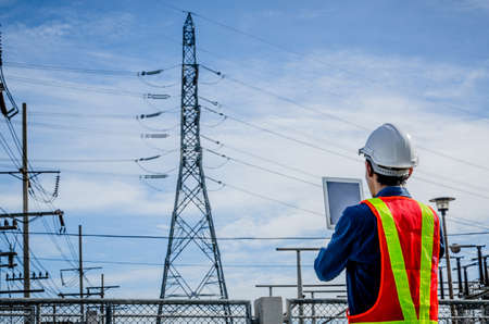 Engineers use the tablet at the high voltage pole against the blue background. Stock fotó