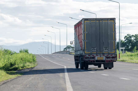 Commercial trailer truck in motion on Thailand freeway, cargo transportation.