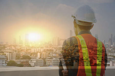 Engineer close-up photos and looking at the city, double exposure, big city view, wide sunset effect, your business message area Stock fotó