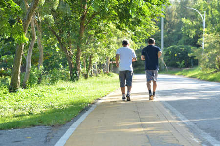 Two elderly men jogging in the park in the morning