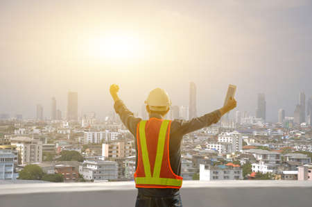 Engineers proudly raise their hands on the job site against the sunrise with the city background. Stock fotó