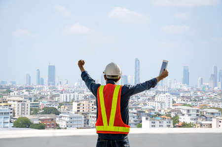 Engineers proudly raise their hands on the job site with the city background.