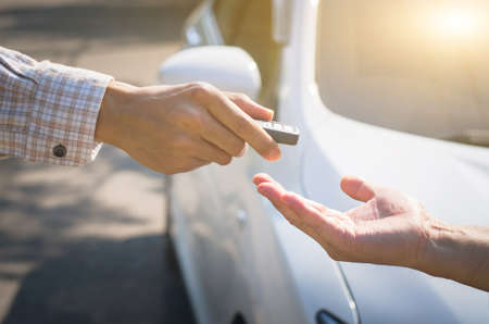 man who is picking up the smart key with his hand