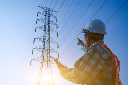 Electrical engineer holding and using a digital tablet, Engineer pointing at high voltage power pylon against sunset background