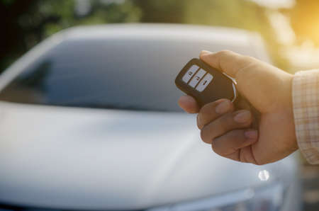 Car remote control by smart key, Hand holding smart key to lock doors of white car Stock fotó