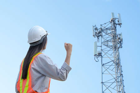 successful female engineer standing at the background of the communication tower
