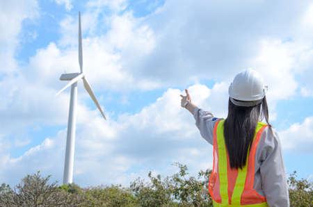 Female engineer pointed to the wind turbine at the wind turbine power station.