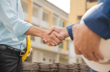 Engineers shaking hands at construction site with building background
