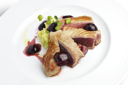 plato de pescado: Pescado Plato del filete de atún con cerezas en el puerto y puré de papas en un plato blanco