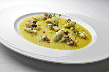 herba: Fish Dish Cream of Jerusalem artichokes with saffron and squid with Herbs in white plate