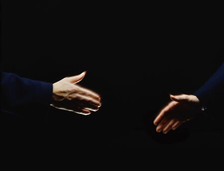 handclasp: Two men Approaching Handshake Moving in black background Stock Photo