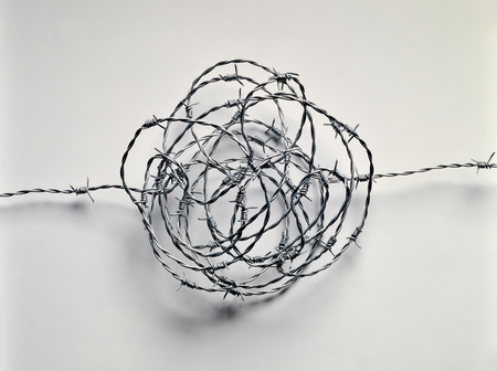 turmoil: Skein of barbed wire on white plane