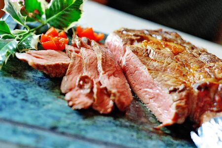 Entrecote grilled sliced with tomatoes on blue stone board 写真素材