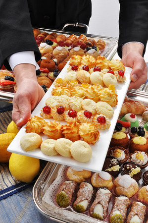 buttery: Buttery - Detail of Tray with assorted Pastries with hands Waiter
