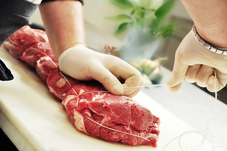 Detail of Hands that Tie Roast Meat on cutting board 写真素材
