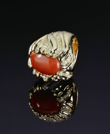 red stone: Gold Ring with Diamonds and Coral on Black background Stock Photo
