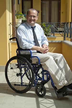 paraplegico: El hombre en una silla de ruedas en el hogar Foto de archivo
