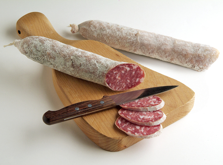 grocer: whole and cut Salami on cutting board with knife
