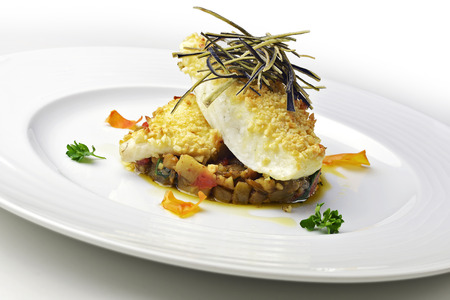 Fish dish, fillet of turbot in an almond crust on chopped eggplant and stewed with eggplant chips Banco de Imagens