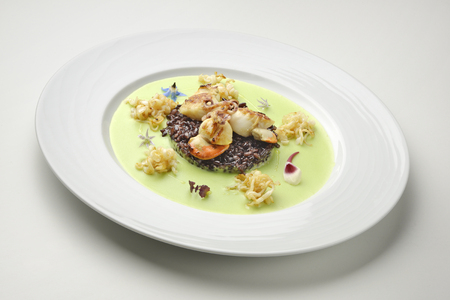 crusted: Appetizer of braised scallops and black rice on pea cream
