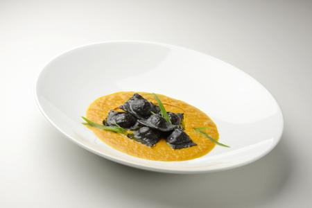 stockfish: Isolated Pasta dish blacks ravioli stuffed with stockfish Stock Photo