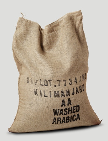 Jute sack filled with label African coffee on white 写真素材