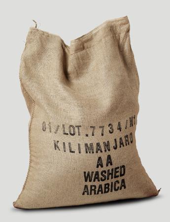 sacco juta: Sacco di iuta pieno di etichetta caffè africano su bianco Archivio Fotografico