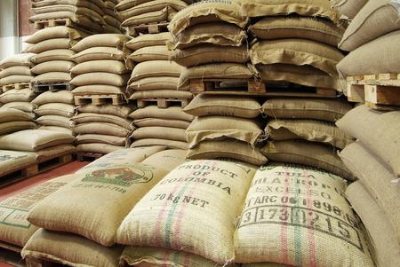 Stock burlap sacks full of coffee in warehouse