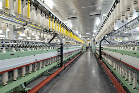 Deep perspective of textile spinning machine in factory Editorial