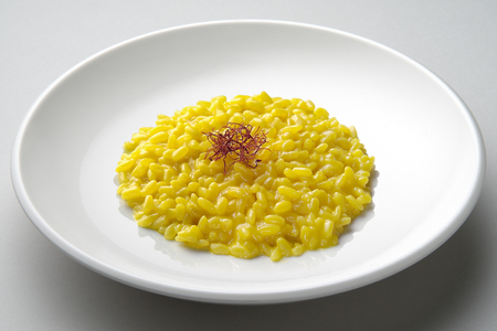 Saffron risotto dish isolated on grey plane