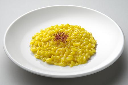 Saffron risotto schotel geïsoleerd op grijs vlak