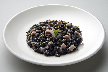 Dish of risotto with squid ink isolated on grey plane