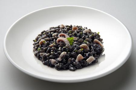 Schotel van risotto met pijlinktvisinkt die op grijs vliegtuig wordt geïsoleerd