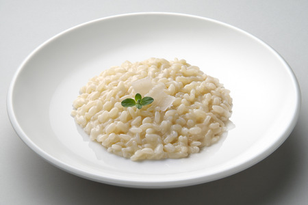 Dish of risotto with cheese isolated on grey plane