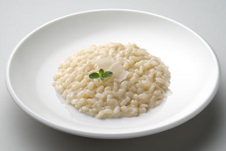 Schotel van risotto met kaas die op grijs vliegtuig wordt geïsoleerd