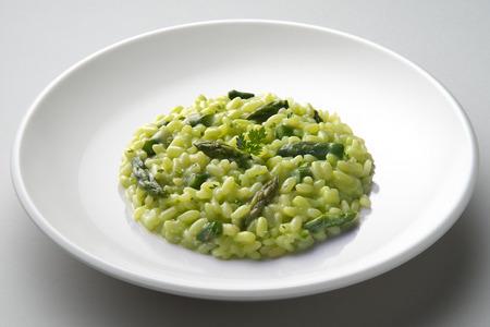 Schotel van risotto met asperge op wit vliegtuig wordt geïsoleerd dat