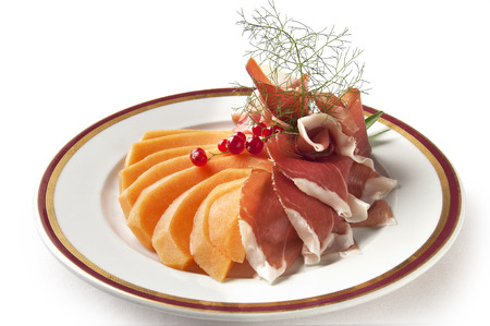 parma ham: Appetizer dish of Parma ham and melon with currants isolated on withe