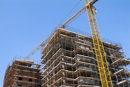unfinished building: Residential Construction site with scaffolding and crane