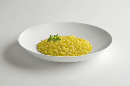 Bowl with saffron risotto isolated on white table