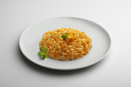 Plate of risotto with pumpkin isolated on white table Stock Photo