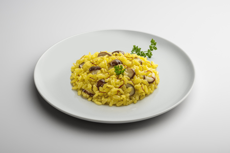 Plate of risotto with saffron and mushrooms isolated on white table