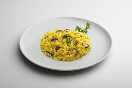 Plaat van risotto met saffraan en paddestoelen die op witte lijst worden geïsoleerd
