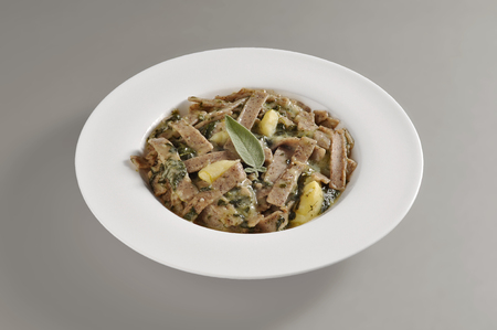 Round dish with a portion of pizzoccheri isolated on grey background