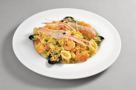 Dish with a portion of fish paella isolated on grey background 写真素材