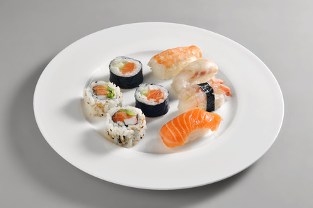 Round dish with a portion of sushi isolated on grey background